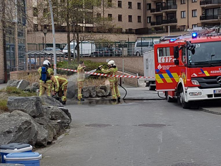De brandweer maakt de kledij van de collega's vrij van chloorgas na de interventie, met behulp van water.