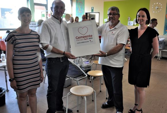 Het gemeentebestuur, hier vertegenwoordigd door schepenen Eddy Soetewey (N-VA), Anne Troch (Open Vld) en Ellen Brits (Open Vld), ontvangt de titel 'Gemeente met een hart'.