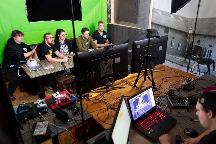 Vier gamers én een masseuse (uiterst links) in actie tijdens de game-marathon in Aalst.