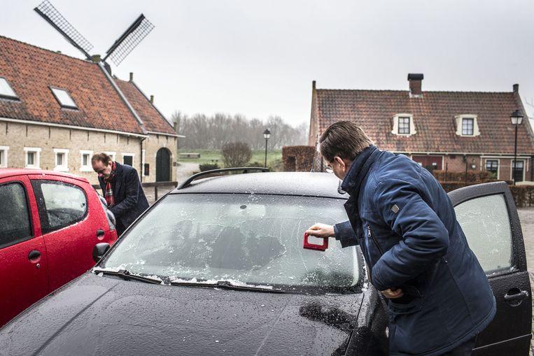 Automobilisten krabben ijzel van hun autoruiten in het vestingdorpje Bourtange. Het KNMI waarschuwde automobilisten in het noordoosten van het land voor gladde wegen en een verhoogde kans op ongelukken. Beeld ANP