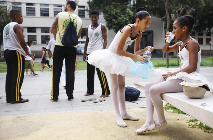 Jonge Braziliaanse ballerina's pauzeren na een optreden op straat in de buurt van de Maua Plaza in Rio de Janeiro. De meisjes proberen geld in te zamelen met straatuitvoeringen om hun droom te volgen en ballet in Duitsland te studeren. Foto Mario Tama