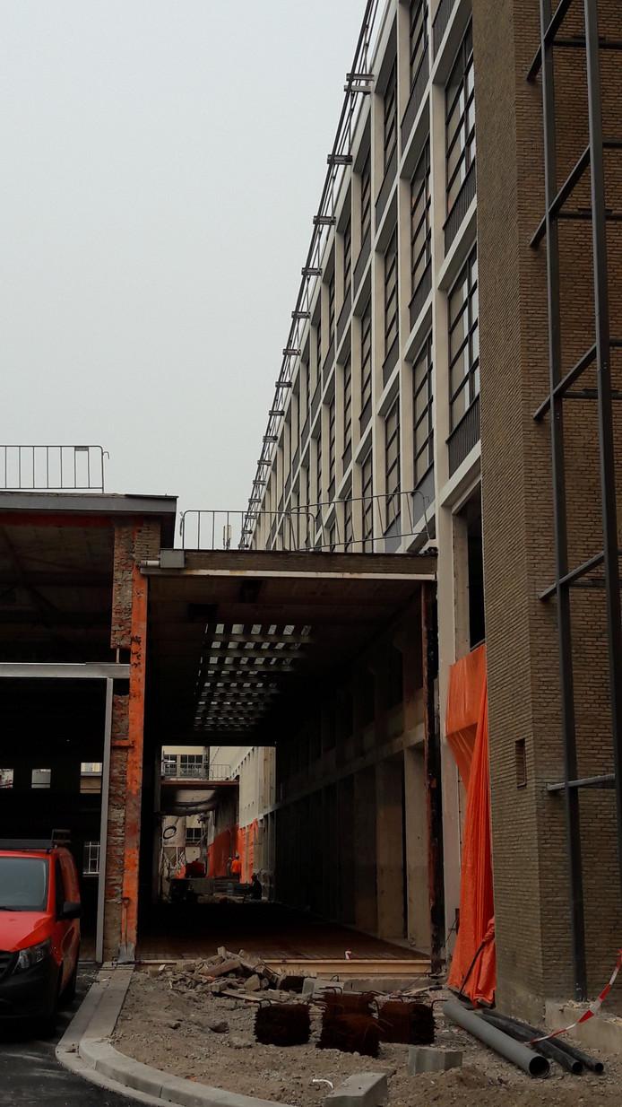 Tussen de industriële hallen en het hoofdgebouw Strijp-TQ komt een transparante gang.