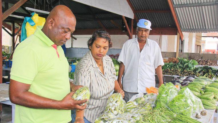 De verbitterde Chander Parsoe (links) en Suresh Pietamber op de lokale markt. 'Door de inflatie kom je maar met twee zakjes spullen thuis.' Beeld Luzmila Samson