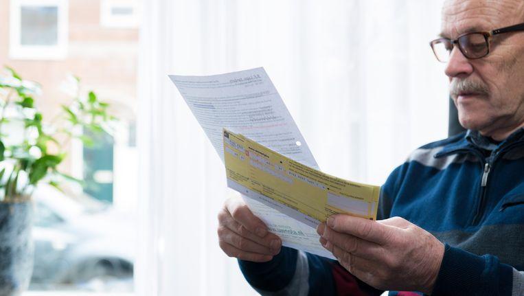 Een gepensioneerde man neemt een stapeltje rekeningen door. Beeld anp