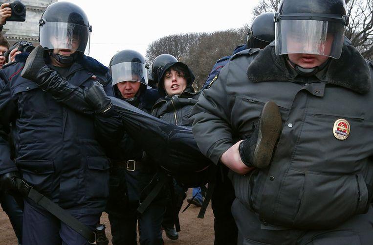 Oproerpolitie voert een demonstrant weg in Sint Petersburg, vandaag. Beeld ap