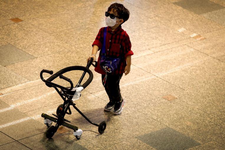 Een jongen in de luchthaven van Beijing. Beeld EPA