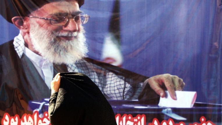 Een Iraanse vrouw trekt haar chador (een lichaamsbedekkend gewaad) recht terwijl ze langs een poster van geestelijk leider Ali Khamenei loopt. ©ANP Beeld