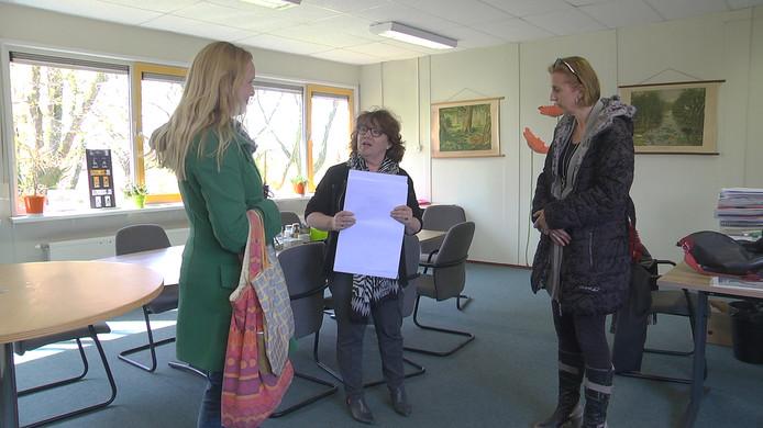 Mieke Steenhof (l) en Dorien Striekwold (r) overhandigen handtekeningen aan bestuursvoorzitter Ivon de Wilde.
