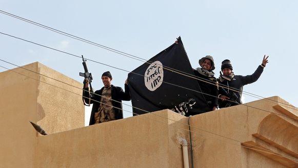 Iraakse soldaten tonen de vlag van IS nadat ze een bastion van de terreurgroep in Mosoel hebben veroverd.
