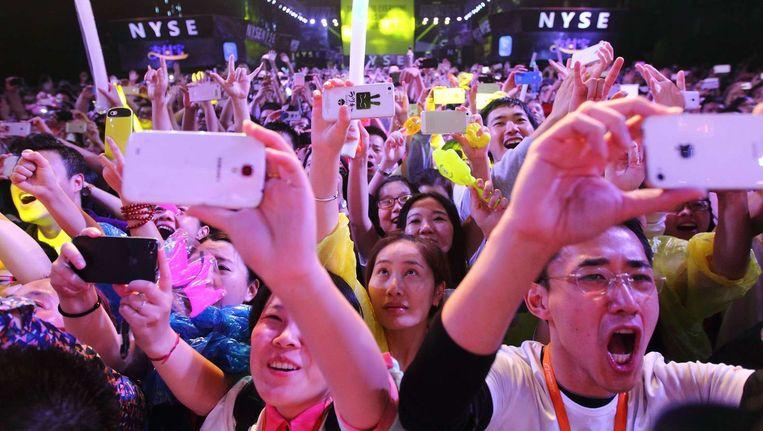 Personeel van Alibaba juicht op het moment dat het aandeel live gaat op de beurs van New York. Beeld afp