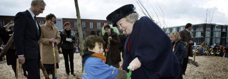 Beatrix plant een boom en krijgt hulp van jonge bewoner van IJburg. (ANP) Beeld
