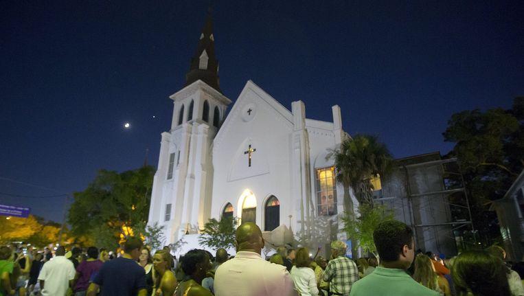 Mensen luisteren naar gospel muziek buiten de Emanuel-kerk, waar zich afgelopen week een bloedbad afspeelde. Beeld reuters