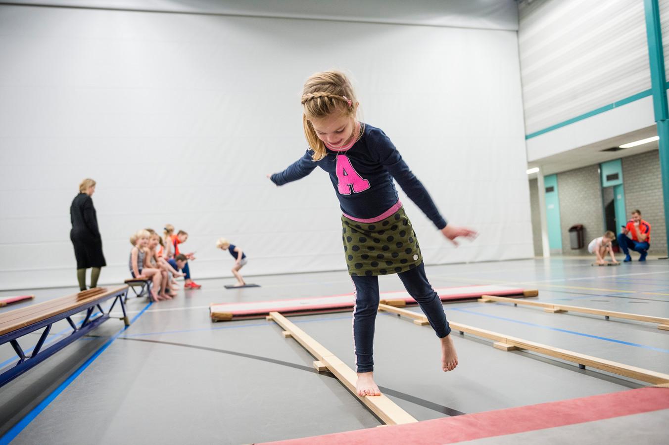 Een leerling op de alternatieve evenwichtsbalk tijdens de test in het kader van het project voor meer en beter bewegen.