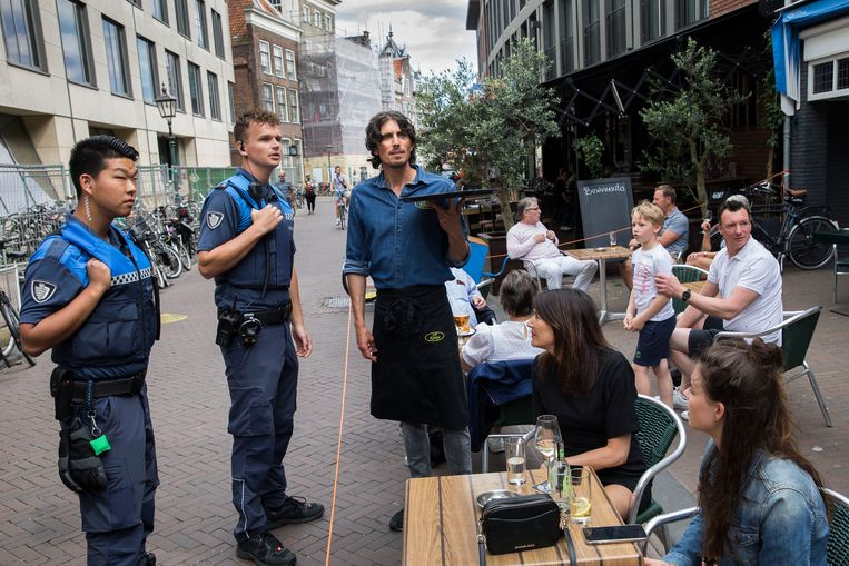 Twee BOA's in het centrum van Haarlem spreken een ober aan omdat de mensen op het terras niet op 1,5 meter afstand van elkaar zitten.  Beeld Arie Kievit