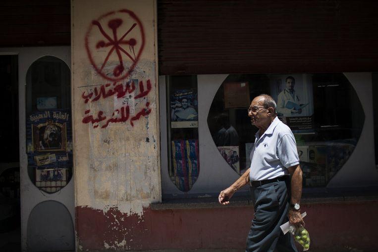 Een Egyptische man loopt langs een apotheek waarop een anti-christelijk teken is aangebracht. Beeld ap