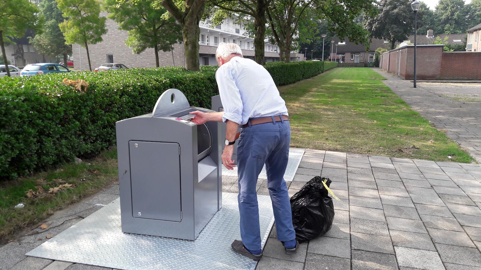 Een bewoner (86) van de Wilderen in wijk Heusdenhout met een zak restafval naar de ondergrondse container.