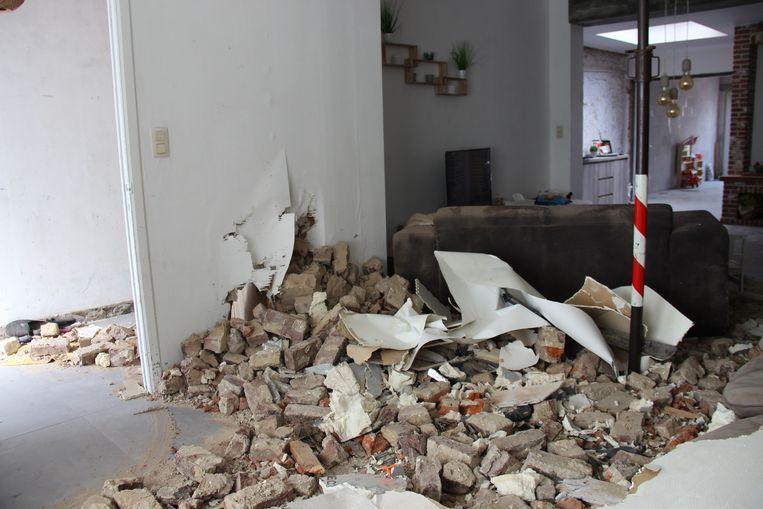 De bakstenen zijn in de living van het huis beland, zelfs in de gang is schade.