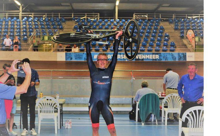Alex Van Breedam trots met zijn fiets in de lucht.