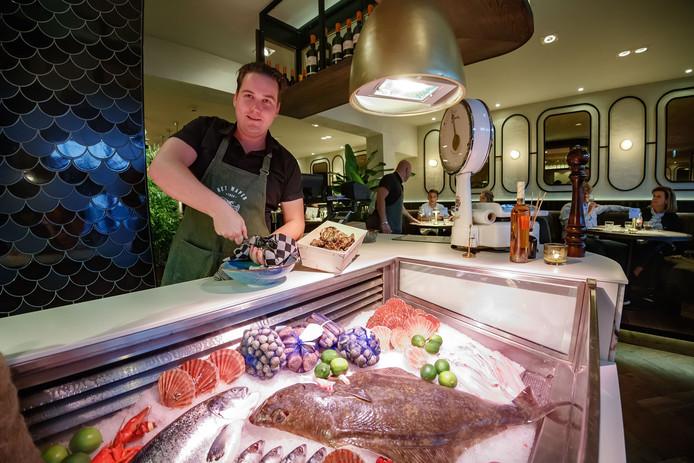 Bedrijfsleider Ferry van der Graaf achter de koeltoonbank vol verse vis.