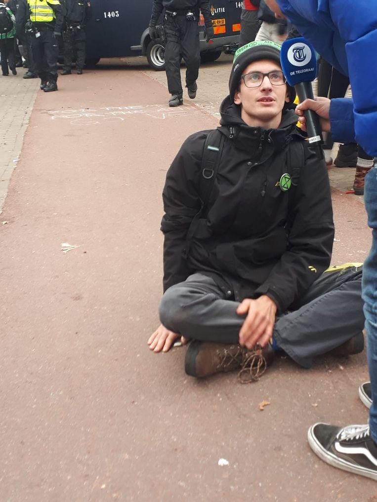 Een demonstrant lijmde zijn hand vast aan de grond. De politie kwam ter plaatse met aceton om de man los te maken. Beeld Bart van Zoelen