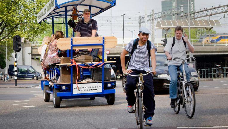 Een groepje buitenlandse toeristen fietst op een bierfiets door Amsterdam. Beeld anp