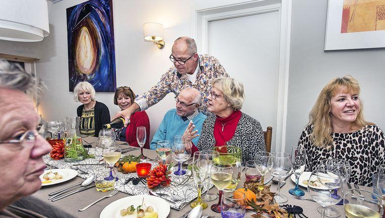 Herman Duijndam bedient zijn gasten in zijn huiskamerrestaurant in Amsterdam-Noord. Beeld Guus Dubbelman
