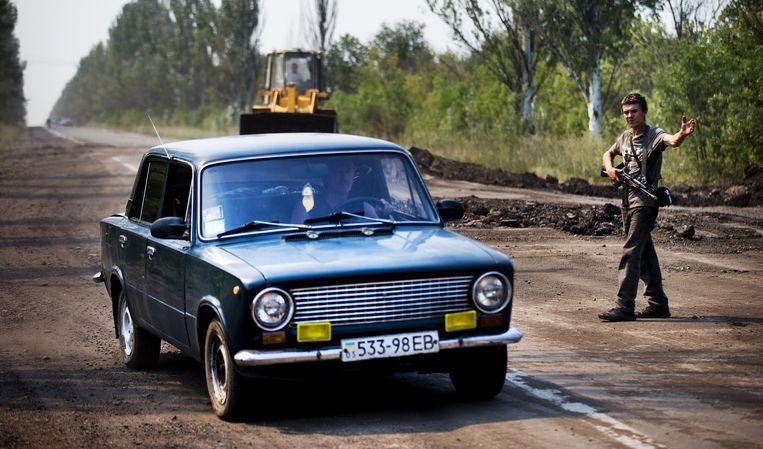 Een separatist houdt de wacht bij een checkpoint op de weg tussen Donetsk en het rampgebied van de MH17. Beeld anp