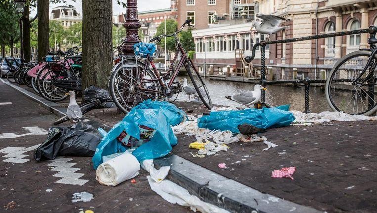 Meeuwen en duiven struinen door het afval op de hoek van de Staalstraat en de Kloveniersburgwal Beeld Eva Plevier
