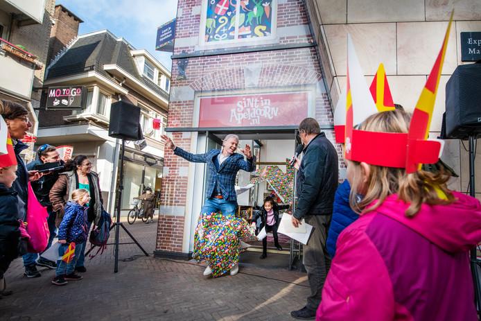 Wethouder Jeroen Joon springt door het inpakpapier. Hij wordt gevolgd door Sibel Ozcan, kinderburgemeester van Apeldoorn. Het Inpakhuis Sinterklaas aan de Mariastraat is geopend.