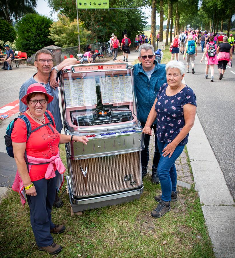 Op de tweede dag van de Vierdaagse in Nijmegen - de Dag van Wijchen - geeft Henk Donkers uit Asten-Heusden (links) met zijn jukebox de lopers een muzikale oppepper.