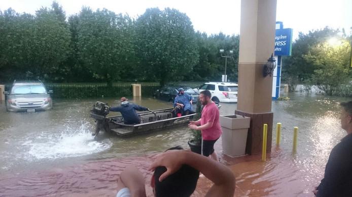 Er viel zoveel water dat Amerikanen met een bootje door de straat varen.