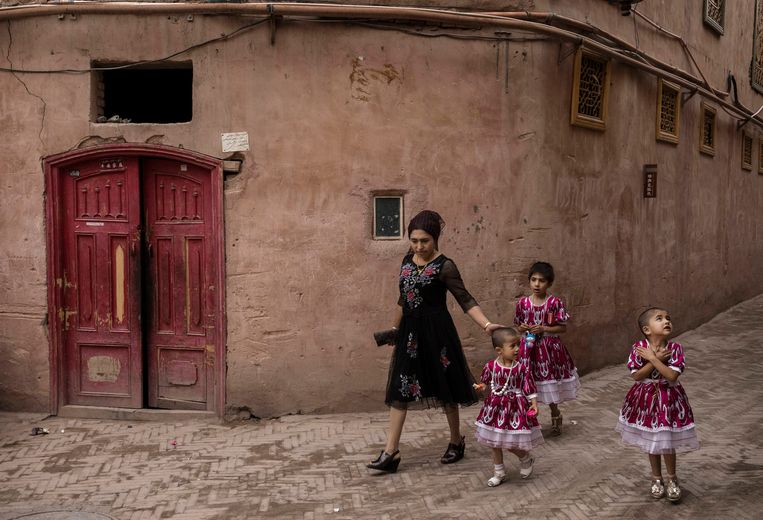 Een vrouw  met haar kinderen in de straten van Kashgar, het culturele hart van de provincie Xinjiang. Beeld Kevin Frayer / Getty Images
