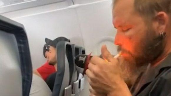 Een man steekt zijn sigaret aan tijdens een vlucht