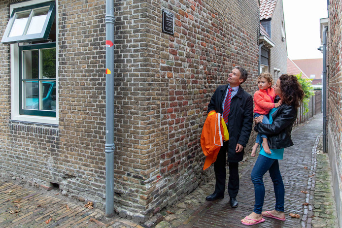 Burgemeester Huub Hieltjes (links) en Willemien Mallekote met dochtertje Zoë kijken naar het  naambordje van de slop van Jan Oele.