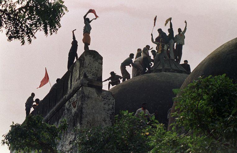 Hindoe-nationalisten schreeuwen en zwaaien met vlaggen op de in 1992 verwoeste moskee in Ayodhya.  Beeld  AFP