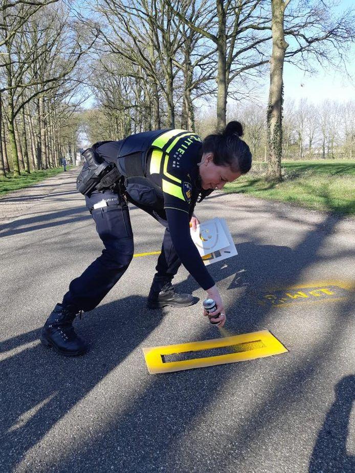 Een agent spuit met gele verf een waarschuwing op het wegdek in de Gravenallee.