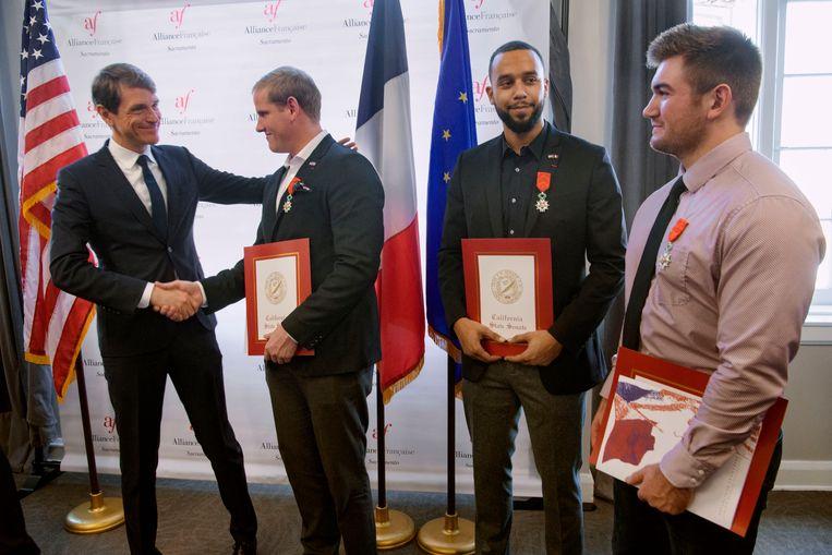 De Franse consul-generaal Emmanuel Lebrun-Damiens feliciteert het drietal.