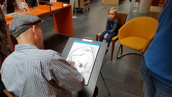 Lange rijen bij karikaturist Thijs Wessels tijdens het kinderboekenweekfeest in de Bibliotheek Hengelo.