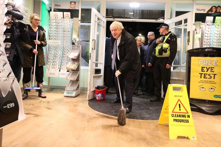 En dweilen kan hij ook! Johnson helpt bij de schoonmaak na de overstromingen in Matlock in noorden van Engeland.