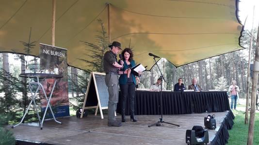 Latere winnaar Ron Reitsma toont presentator Juila Marijn zijn attributen.