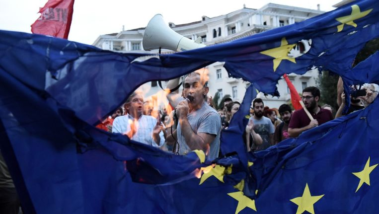 Griekse demonstranten steken de Europese vlag in brand in de stad Thessaloniki.