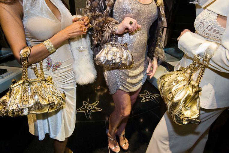 Jackie (41) en haar vriendinnen dragen Versace-handtassen tijdens een besloten openstelling van de Versace-winkel, Beverly Hills, 2007. Beeld Lauren Greenfield / Fotomuseum Den Haag