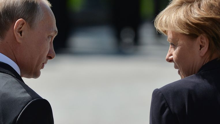 Merkel en Poetin lopen weg na de kranslegging in Moskou. Beeld ap