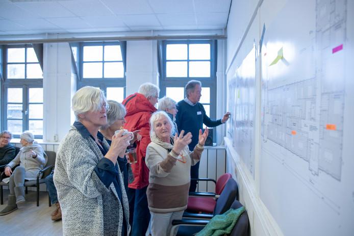 Potentiële bewoners van de woongroep in Ede bekijken in de voormalige Bergansiuskazerne de tekeningen van de nieuwe appartementen.