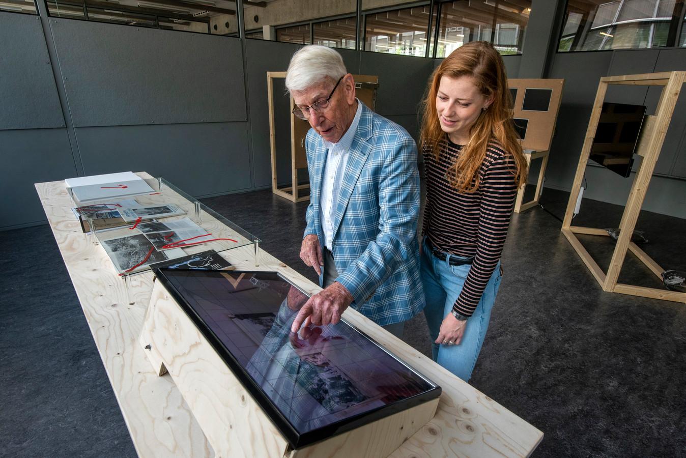 Studente Marlou Bleijenberg (24) kijkt toe terwijl haar opa Piet Rijkaart bladert door een boek over de oorlog.
