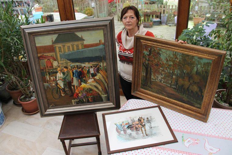 Karin Beel met enkele van de schilderijen van haar vader Leon.
