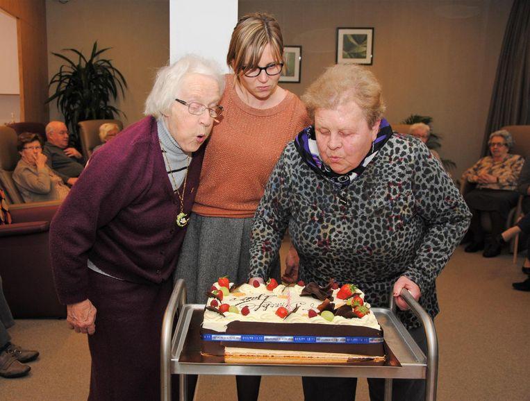Gasten van 't Binnenhof snijden de taart aan.
