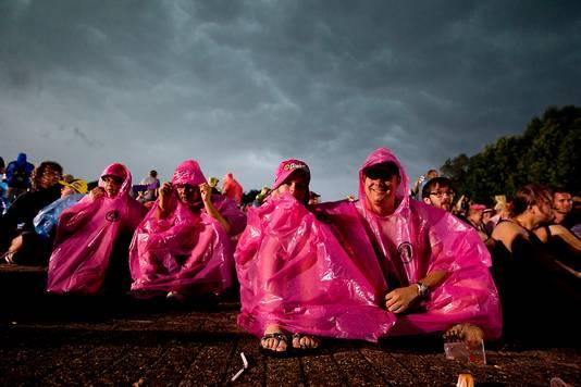 Festivalbezoekers schuilen voor de regen.