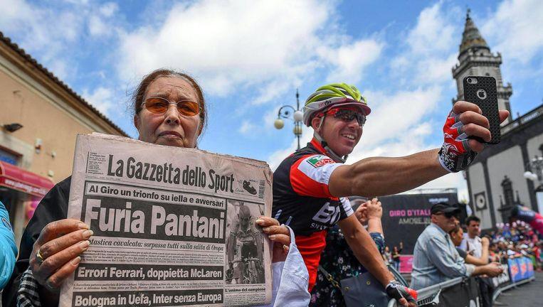 Een toeschouwer houdt een krant omhoog ter nagedachtenis aan Pantani. Beeld epa