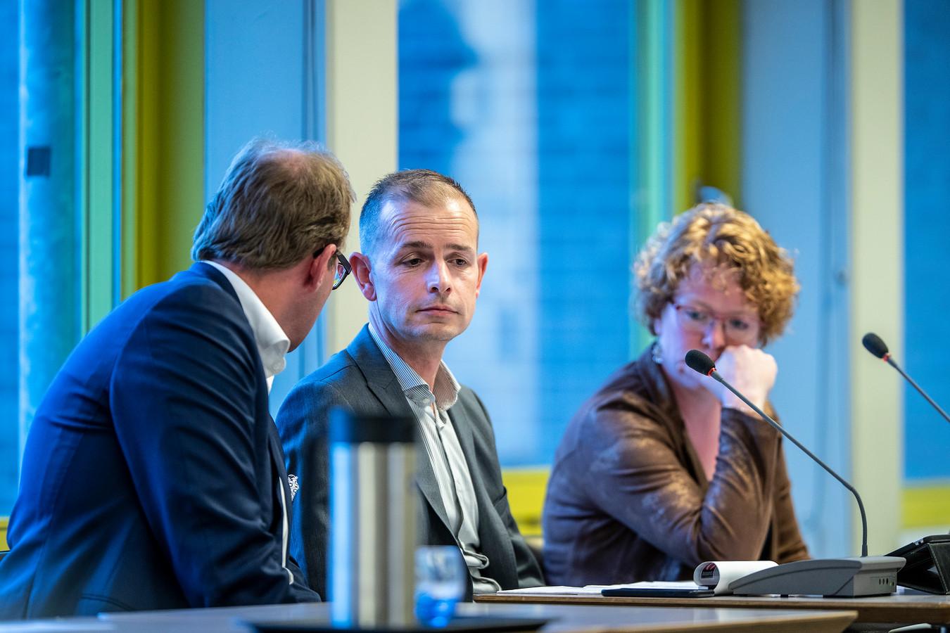 Mark Boumans, burgemeester van Doetinchem, fluistert wethouder Jorik Huizinga in dat het misschien beter is het onderwerp van Laborijn van de agenda te halen.